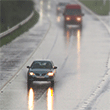 cars driving down wet highway with light rain